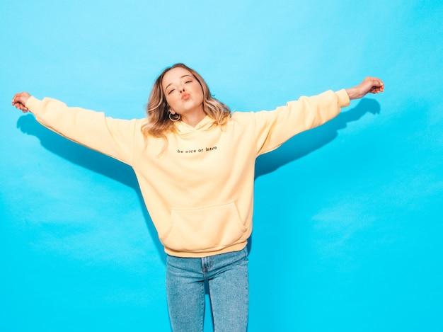 Sexy carefree woman posing near blue wall. positive model having fun.raising her hands Free Photo