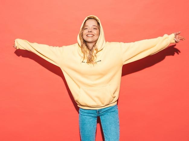 Sexy carefree woman posing near pink wall. positive model having fun.raising her hands Free Photo