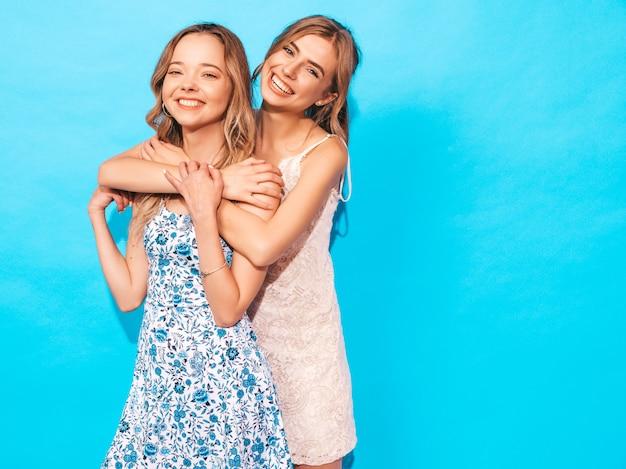 Sexy carefree women posing near blue wall. having fun and hugging Free Photo