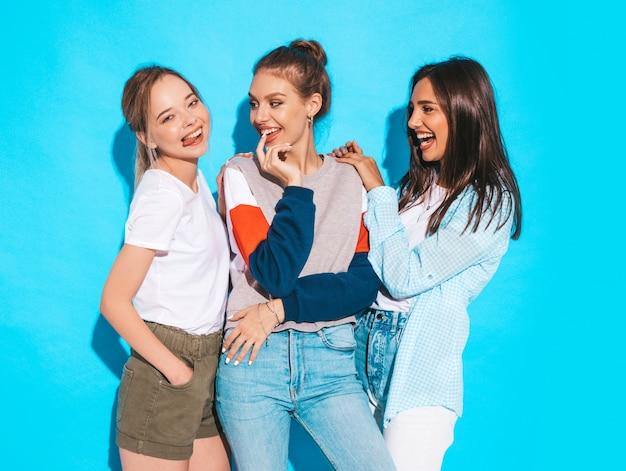 Sexy carefree women posing near blue wall in studio. positive models having fun and hugging Free Photo