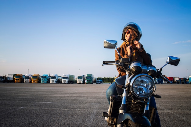 Sexy female motorcyclist sitting on retro style motorcycle and fastening helmet belt before ride Free Photo