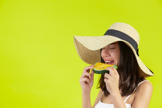 セクシーな女の子は黄色の壁に帽子とシュメール暑い天気でウォーターマロンを食べています。 無料写真