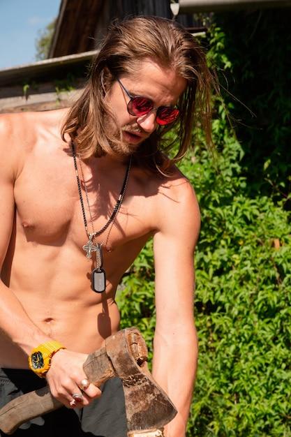 木製チョッパーを保持している裸の胴体とサングラスでセクシーな長髪の若い男。 Premium写真