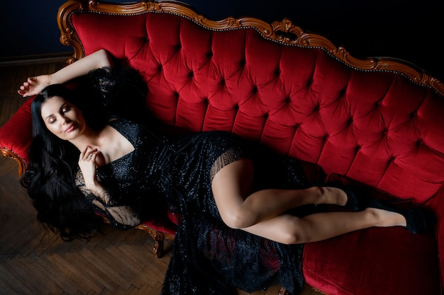 Sexy longhaired brunette caucasian girl with closed eyes is lying on the luxury red sofa dressed in black lace dress Free Photo