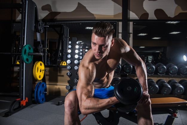 Sexy man in the gym with dumbbells. sporty man Premium Photo