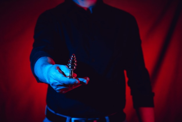 Sexy man holds a bdsm anal plug in his hands. this product is only for adults Premium Photo