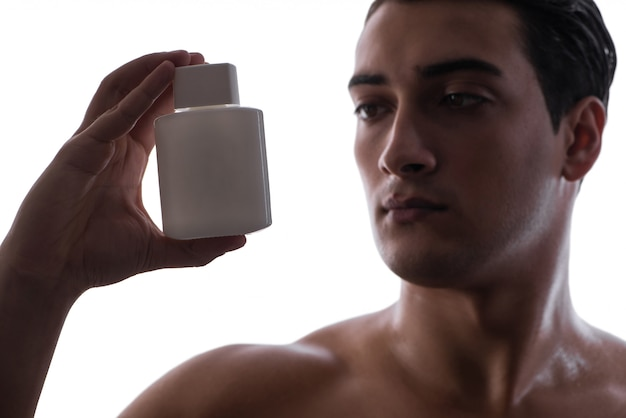Sexy man with bottle of perfume in low key photo Premium Photo