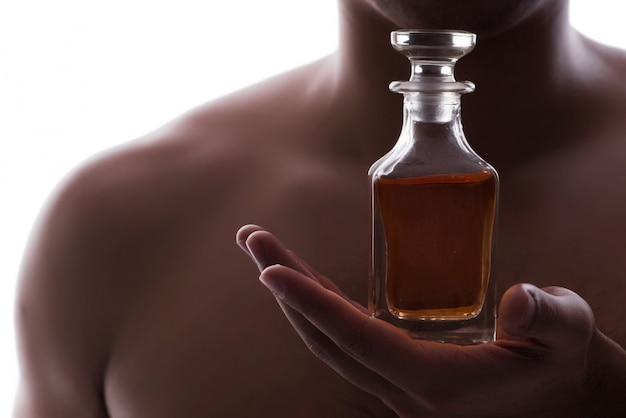 Sexy man with bottle of perfume Premium Photo