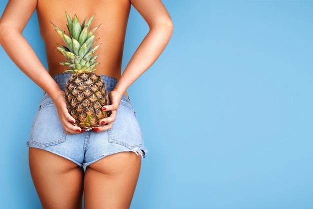 Сексуальная модельная девушка с ананасом на спине Premium Фотографии
