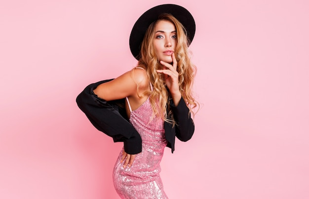 ピンクの壁でポーズ豪華なスパンコールのドレスで完璧な輝くウェーブのかかった髪を持つセクシーなモデル。ナチュラルメイク。完全にセクシーな唇。黒い帽子とジャケット。ファッショナブルな肖像画。 無料写真