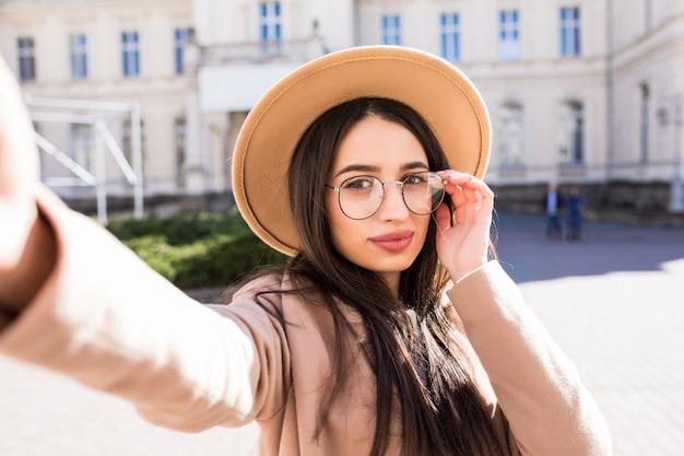 Сексуальная модельная женщина делает селфи на своем новом смартфоне на улице в городе в солнечный день Бесплатные Фотографии