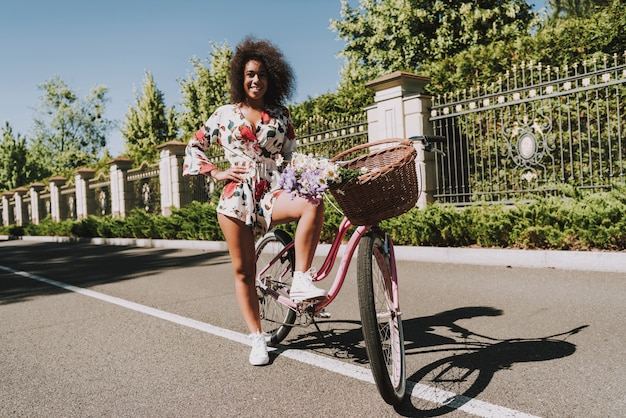 Sexy mulatto girl is standing on bicycle. Premium Photo