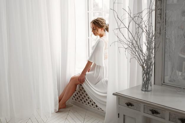 침실에서 속옷에 섹시 한 미소 금발 신부입니다. 세련 된 인테리어와 호텔 방에서 아름 다운 신부의 아침. 입찰 창 근처 흰색에 흰색 속옷이나 잠옷에 젊은 여자 프리미엄 사진