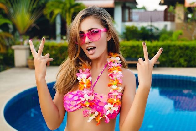 ビキニとピンクのサングラス、ハワイの熱帯の花、カラフルな夏のファッションスタイルを身に着けているプールで楽しんで夏休みのセクシーな笑顔の女性 無料写真