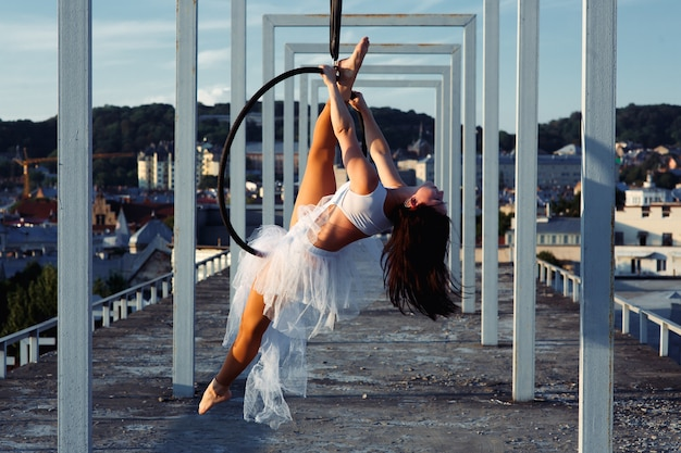 Sexy strong dancer performing on aerial hoop on rooftop Free Photo