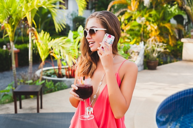 Sexy stylish woman in fashion party outfit on summer vacation with glass of cocktail having fun on pool talking on phone Free Photo