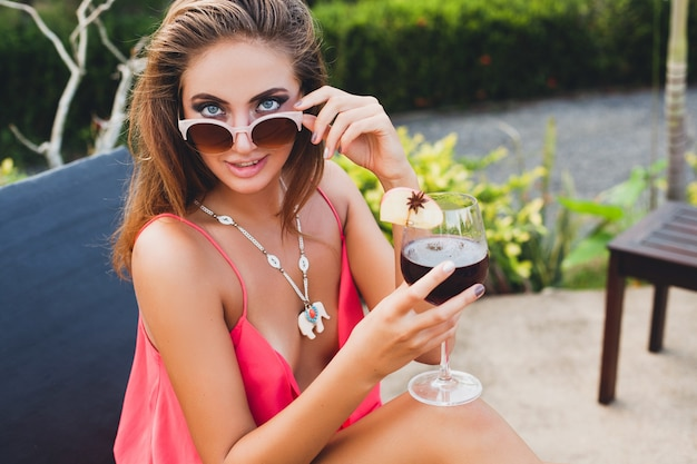 Sexy stylish woman in fashion party outfit on summer vacation with glass of cocktail having fun on pool Free Photo