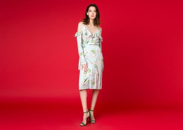 赤いスタジオでポーズ夏のファッショントレンドドレスでセクシーなスタイリッシュな女性 無料写真