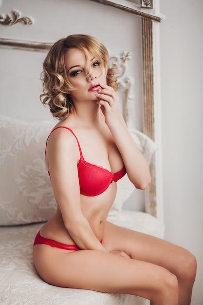 입술에 손으로 빨간 란제리에 섹시 한 물결 모양의 머리 여자. 프리미엄 사진
