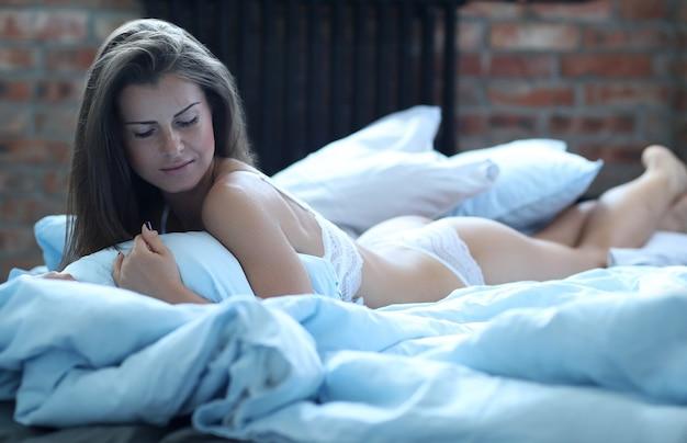 ベッドに横になっているランジェリーのセクシーな女性 無料写真