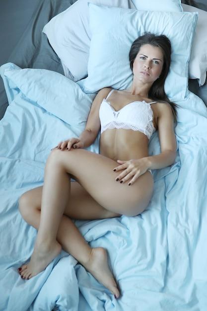Donna sexy in lingerie sdraiata sul letto Foto Gratuite