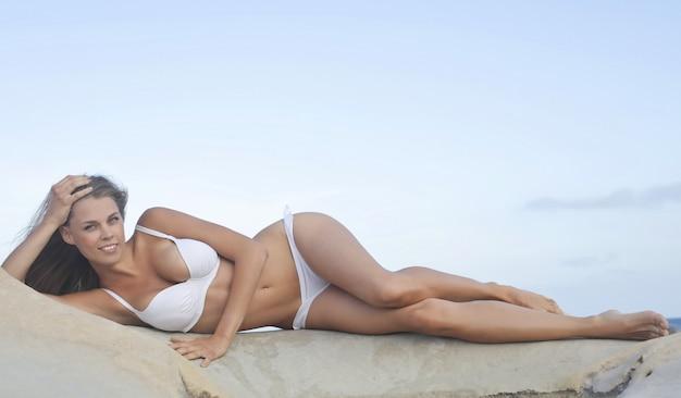 Sexy woman lying on the beach Premium Photo