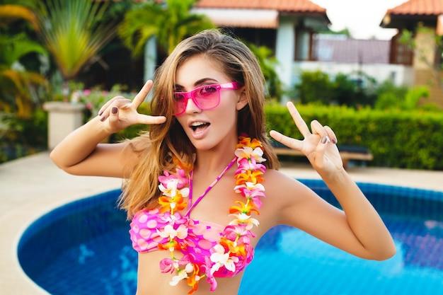 ビキニとピンクのサングラス、熱帯の花、カラフルな夏のファッションスタイルを身に着けているプールで楽しんで夏休みのセクシーな女性 無料写真