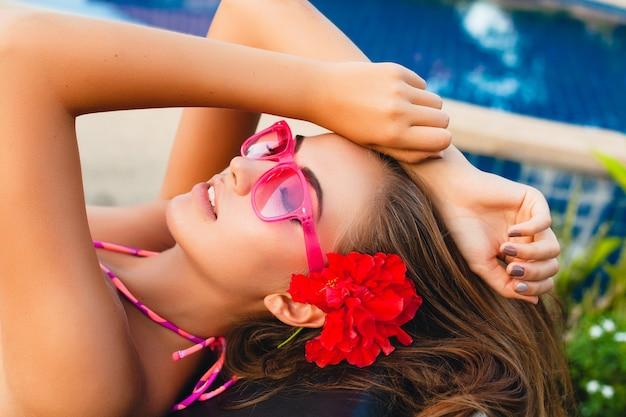 ビキニとピンクのサングラス、熱帯の花、カラフルな夏のファッションスタイルを身に着けているプールで横たわっている夏休みのセクシーな女性 無料写真