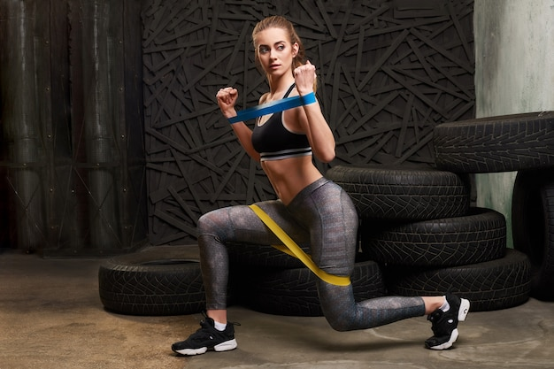 Sexy woman in sportswear using a resistance band in her exercise routine Premium Photo