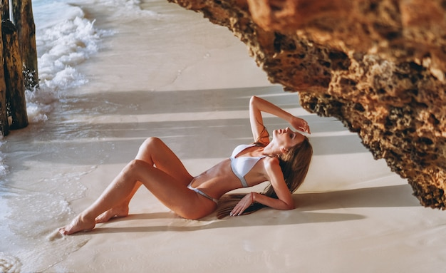 Sexy woman in swim wear lying by the ocean under the caves Free Photo