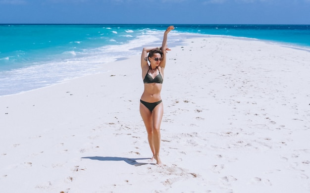 Sexy woman in swim wear standing on sand by the ocean Free Photo