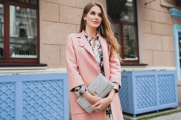 Сексуальная молодая красивая стильная женщина гуляет по улице в розовом пальто, держа в руках кошелек, слушая музыку Бесплатные Фотографии