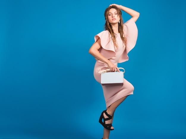 핑크 럭셔리 드레스, 여름 패션 트렌드, 세련된 스타일, 블루 스튜디오 배경, 유행 핸드백을 들고 섹시한 젊은 세련된 섹시한 여자 무료 사진