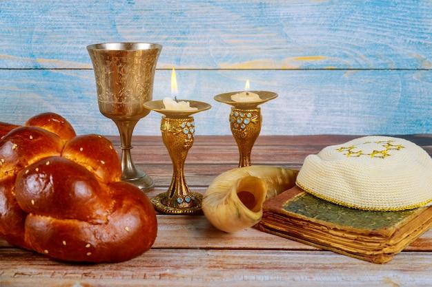 Shabbat challah bread, shabbat wine and candles on the table Premium Photo