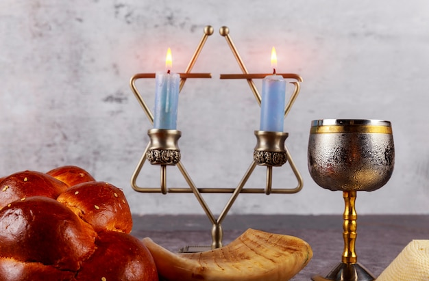 Shabbat with challah bread on a wooden table candles and cup of wine. Premium Photo