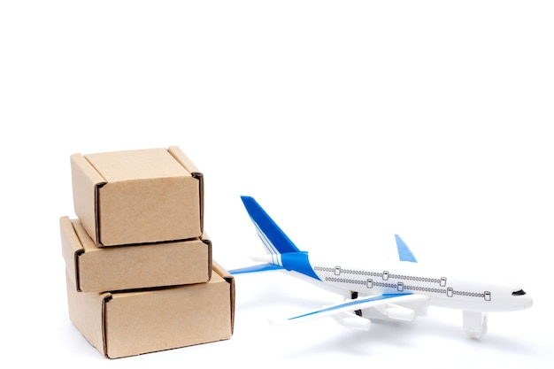 Shadow airplane and stack of cardboard boxes isolated on white background. concept of air cargo and parcels, airmail. fast delivery of goods and products. logistics, connection to hard-to-reach places Premium Photo