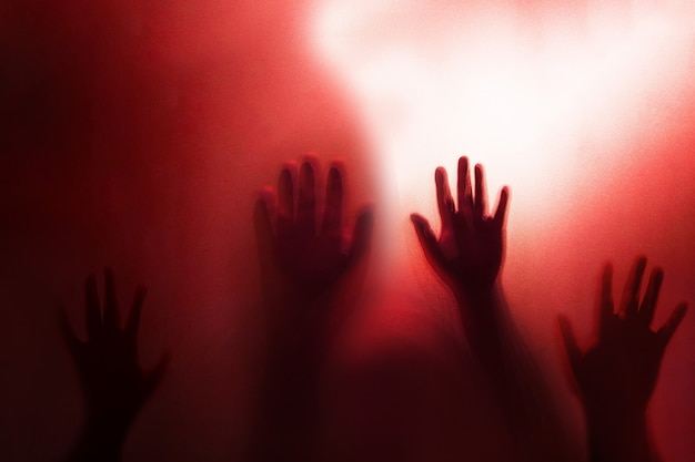 Shadow of the ghost hand behind frosted glass Premium Photo
