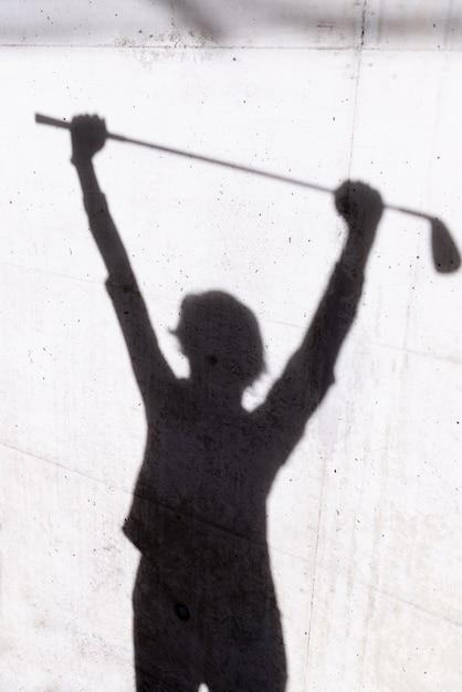 조명 아래 벽에 골퍼의 그림자 무료 사진