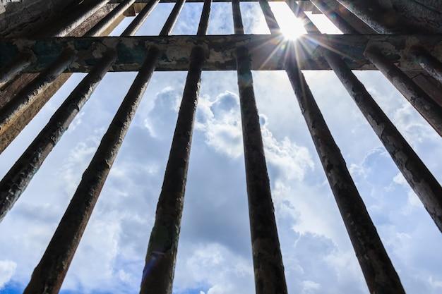 Тень сияет сквозь решетку старой тюрьмы Premium Фотографии