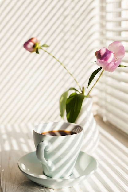 Shadow of window blinds on coffee cup and flower vase Free Photo