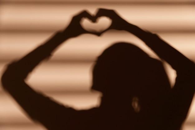 Ombra di donna che fa un cuore Foto Gratuite
