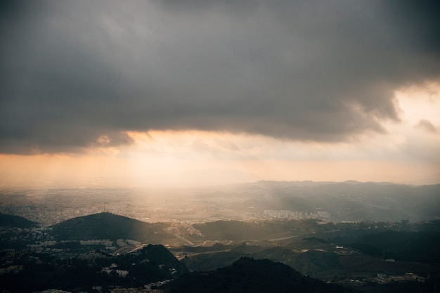 Shaft of light penetrating through dark sky over the cityscape mountain Free Photo