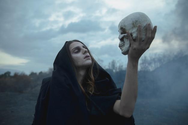 Shakesprearian idea of a man holding a skull Free Photo