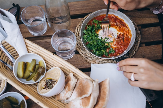 Shakshuka, fried eggs in tomato sauce on the table Free Photo