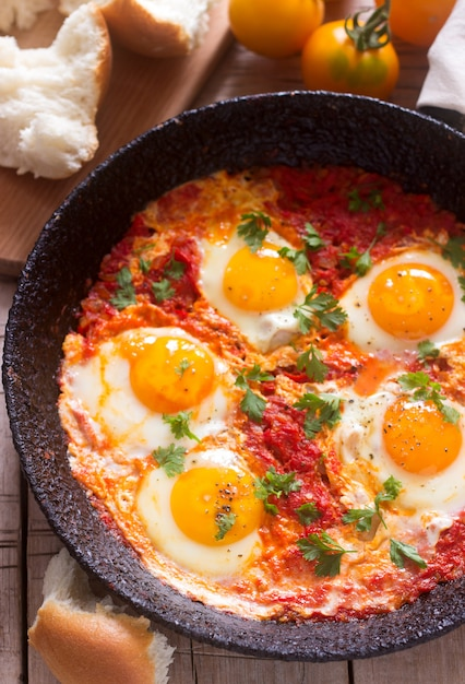 Shakshuka with bread on a wooden table. middle eastern traditional dish. homemade. selective focus. Premium Photo