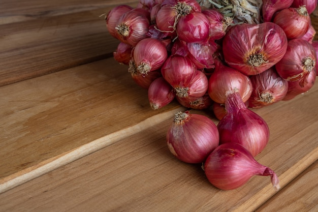 Shallots placed on brown wood. Free Photo