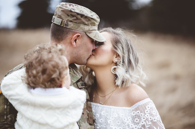 Colpo poco profondo del fuoco di un soldato americano che trasporta suo figlio mentre bacia la sua amorevole moglie Foto Gratuite