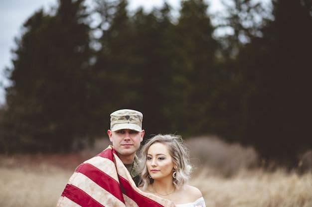 Shallow focus shot di un soldato americano con sua moglie avvolta in una bandiera americana Foto Gratuite