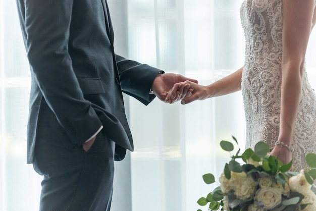 Shallow focus shot of a bride and groom holding hands with each other Free Photo