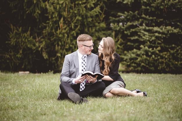 Colpo poco profondo del fuoco di una coppia che parla e gode della reciproca compagnia mentre è seduto in un giardino Foto Gratuite